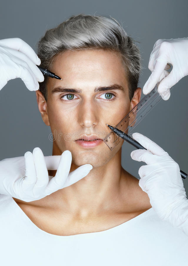Beautician hands trying on where to put surgical signs in front of plastic operation. stock photos