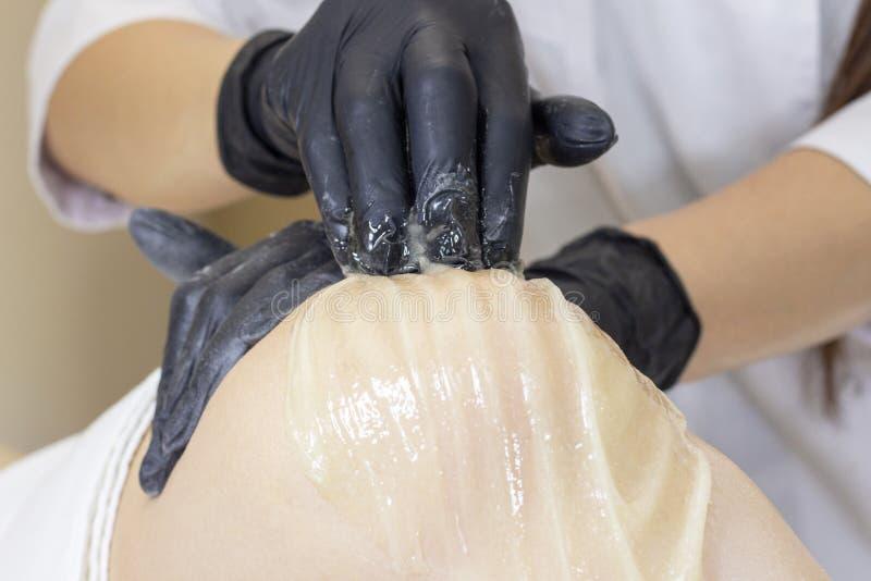 Beautician kobiety depilujące nogi z ciekłym cukierem w zdroju ześrodkowywają zdjęcia royalty free