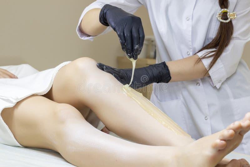 Beautician kobiety depilujące nogi z ciekłym cukierem w zdroju ześrodkowywają zdjęcie stock