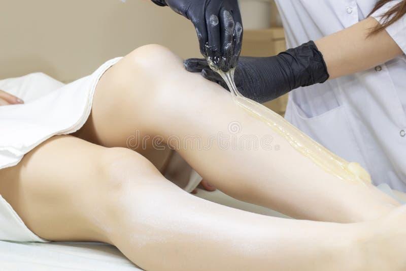 Beautician kobiety depilujące nogi z ciekłym cukierem w zdroju ześrodkowywają obraz stock
