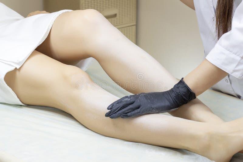 Beautician kobiety depilujące nogi z ciekłym cukierem w zdroju ześrodkowywają fotografia stock
