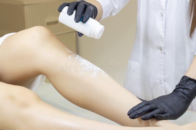 Beautician kobiety depilujące nogi z ciekłym cukierem w zdroju ześrodkowywają zdjęcie royalty free
