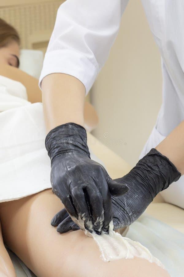 Beautician kobiety depilujące nogi z ciekłym cukierem w zdroju ześrodkowywają Depilacja nogi z cukrow? past? fotografia stock
