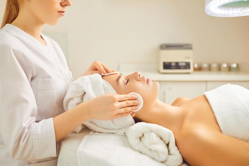 Beautician makes cleaning the face of a woman in the cosmetology office. stock images