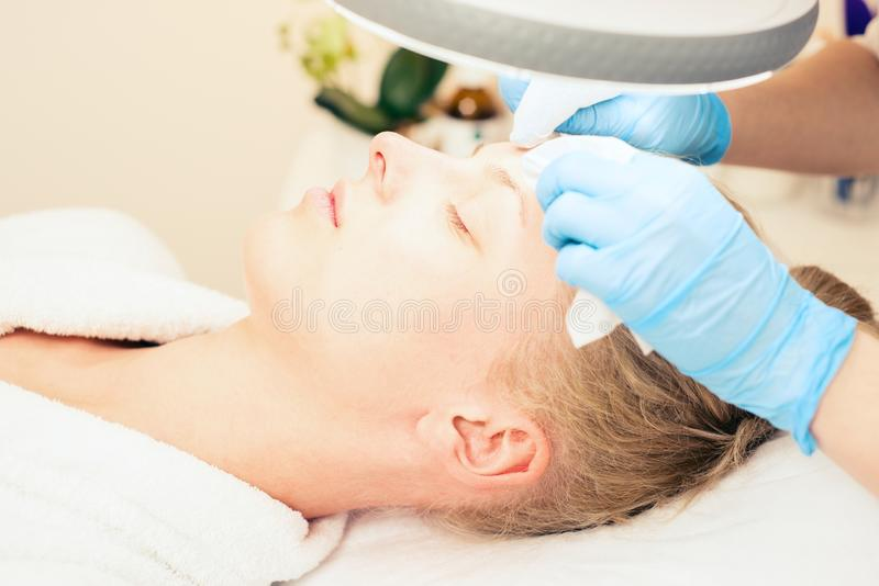 Beautician makes cleansing. female specialist cosmetologist removes comedones. Spa. healthy lifestyle concept royalty free stock photos