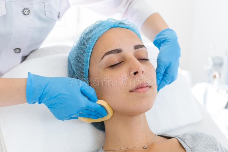 Beautician makes client facial massage yellow sponges royalty free stock image