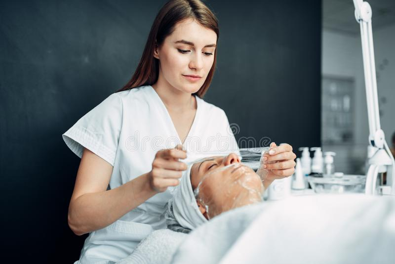 Beautician makes face mask to young woman stock photos