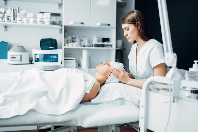 Beautician makes face massage to female patient. Cosmetology clinic. Facial skincare, rejuvenation procedure in spa salon royalty free stock image
