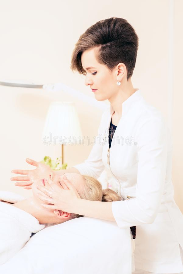 Beautician makes facial massage. cosmetology cabinet. skin care. healthy lifestyle concept royalty free stock image