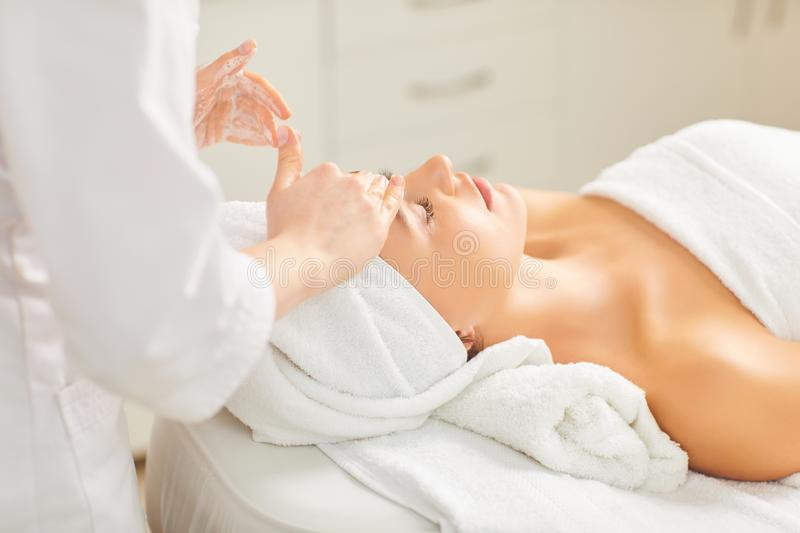 Beautician makes facial massage to the girl. In the cosmetology office royalty free stock images