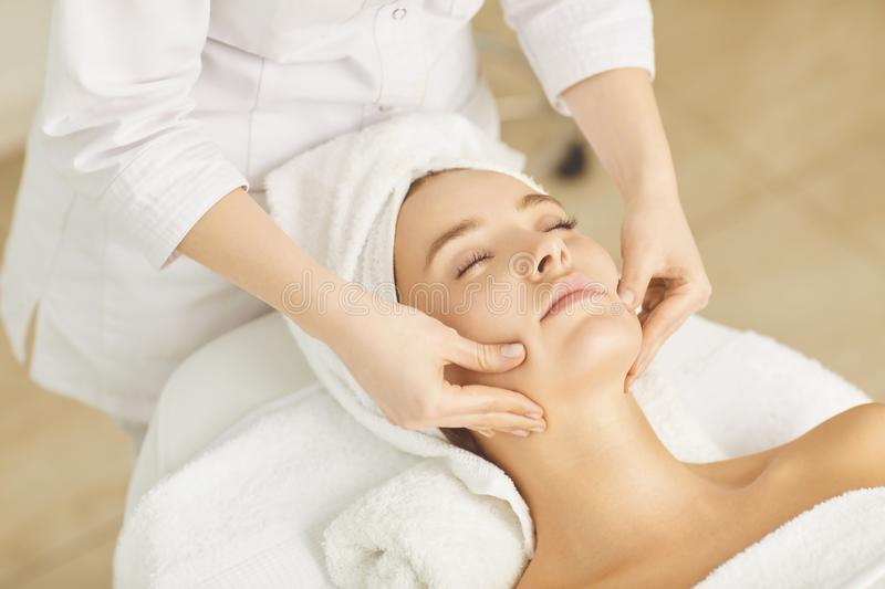 Beautician makes facial massage to the girl. In the cosmetology office stock images