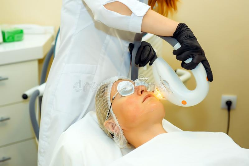 Beautician makes facial rejuvenation procedure for women in the beauty salon. Doctor in medical gloves, patient in special glasses royalty free stock photography
