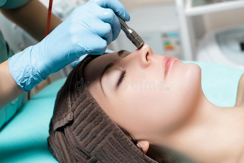 Beautician makes mechanical cleaning of face. Procedure of Microdermabrasion, diamond grinding. royalty free stock photography