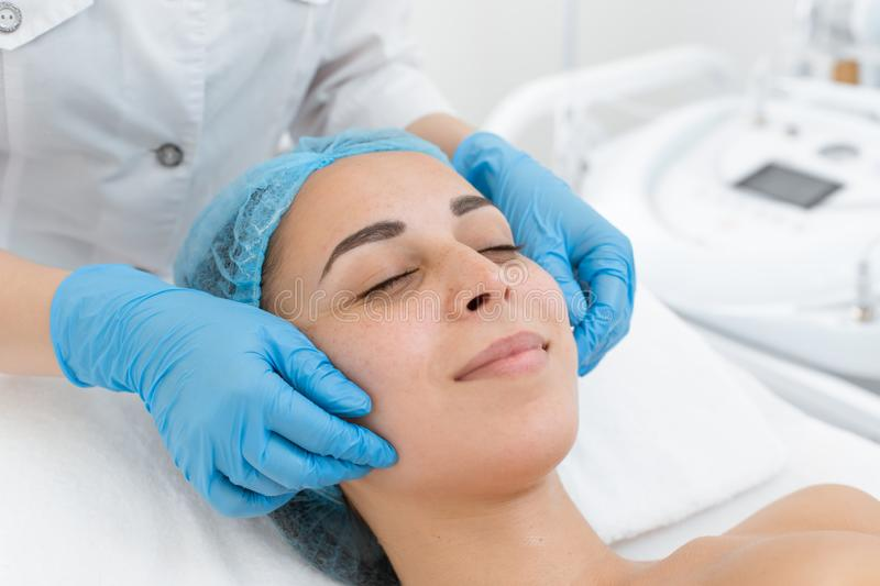 Beautician makes professional massage of the patient`s face. A young girl is undergoing a course of spa treatments in the office royalty free stock images