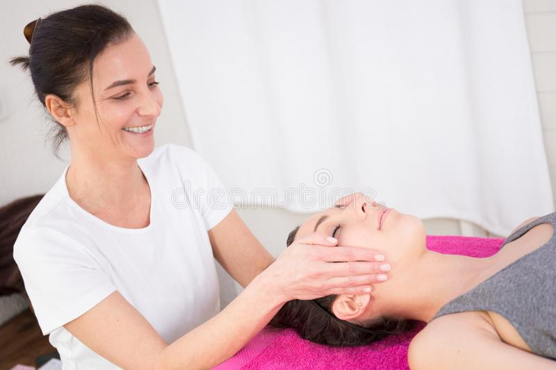 Beautician makes a well-being massage on the head of a pretty young woman stock image
