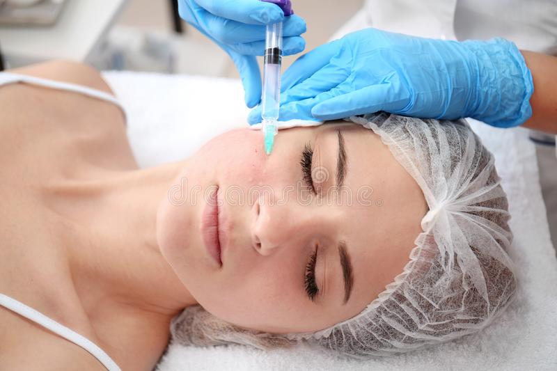 Beautician making injection in woman`s face stock image
