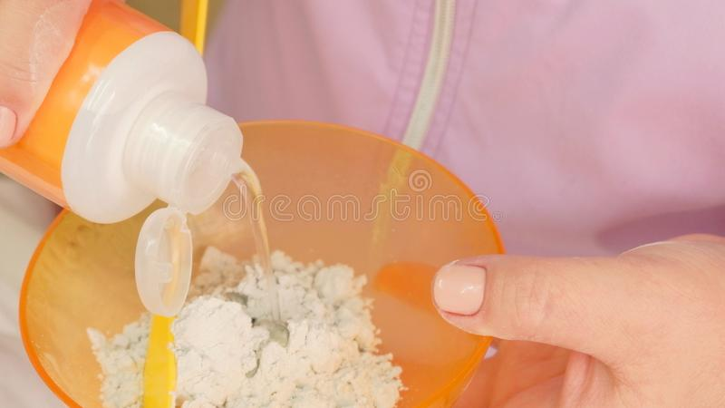 The beautician mixes the lotion with dry algae to get an alginate mask for face and body.  royalty free stock images