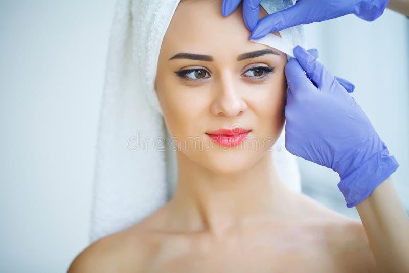 Beautician nawoskuje młodej kobiety ` s brwi w zdroju ześrodkowywa obrazy stock