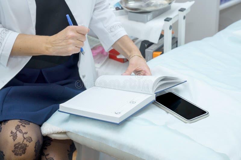 Beautician o doctores haciendo notas en el cuaderno Oficina de los médicos fotos de archivo libres de regalías
