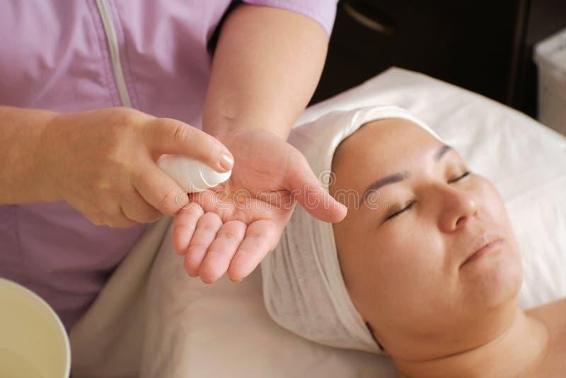 Beautician oliwi ręki z gel stosować je na twarzy kobieta Przygotowanie dla kosmetologii procedur w pięknie obrazy stock