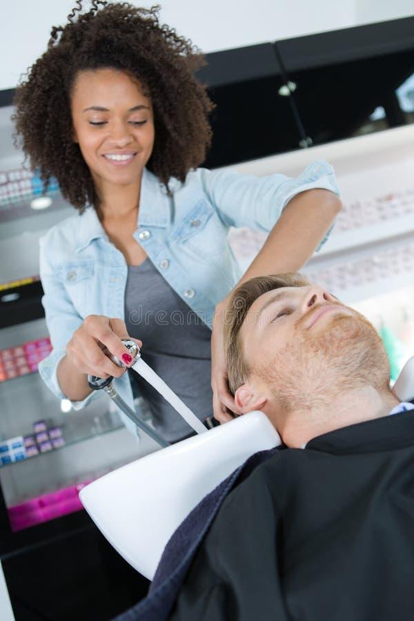 Beautician płuczkowi męscy klienci włosiani w salonie zdjęcie stock