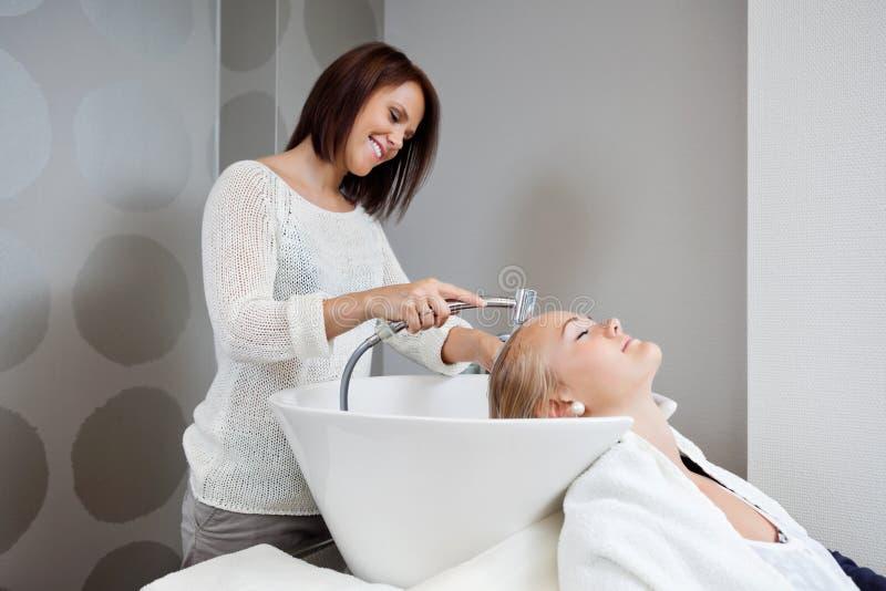 Beautician Płuczkowy włosy klient zdjęcie stock