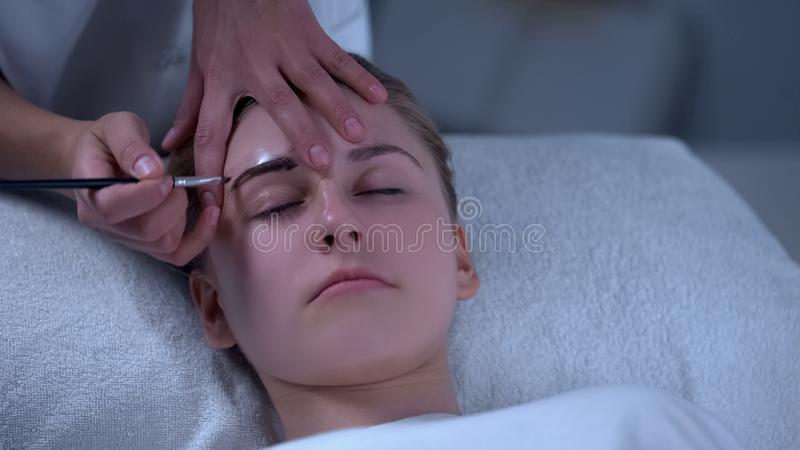 Beautician painting eyebrows with hypoallergenic dye, eyebrow shape correction royalty free stock images