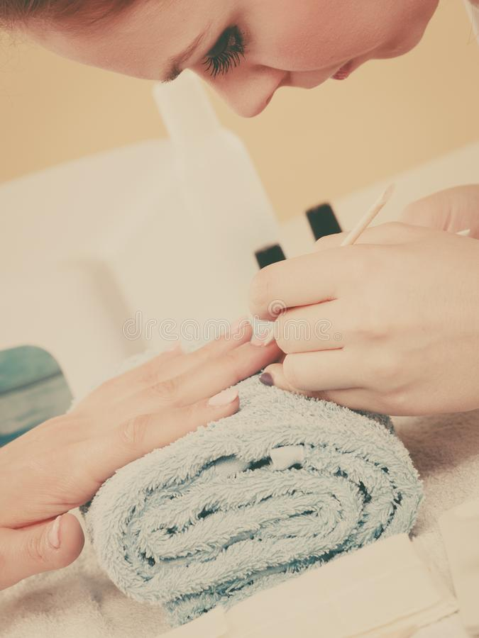 Beautician preparing nails before manicure, pushing back cuticles. Nail care, beauty wellness spa treatment concept. Woman beautician preparing nails before stock photo
