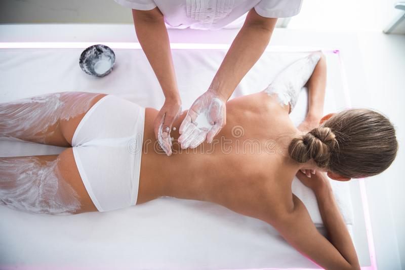 Beautician preparing white clay for applying on girl back royalty free stock image