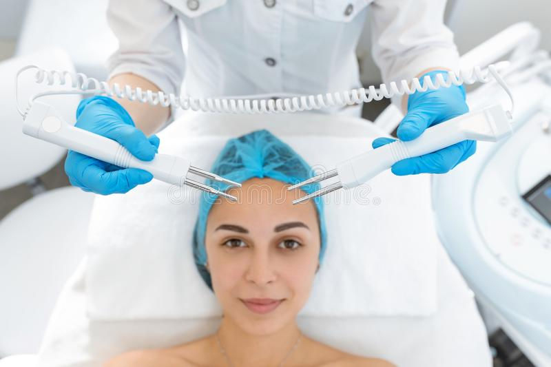 Beautician procedure of microcurrent therapy of the patient`s face. A young girl is undergoing a course of spa treatments in the royalty free stock photos