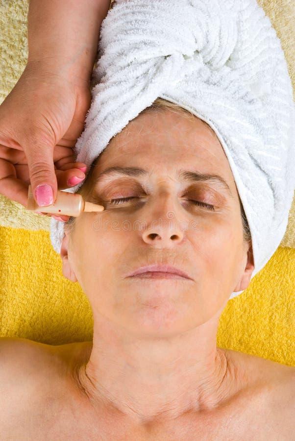Beautician que aplica el suero a la cara mayor imagen de archivo