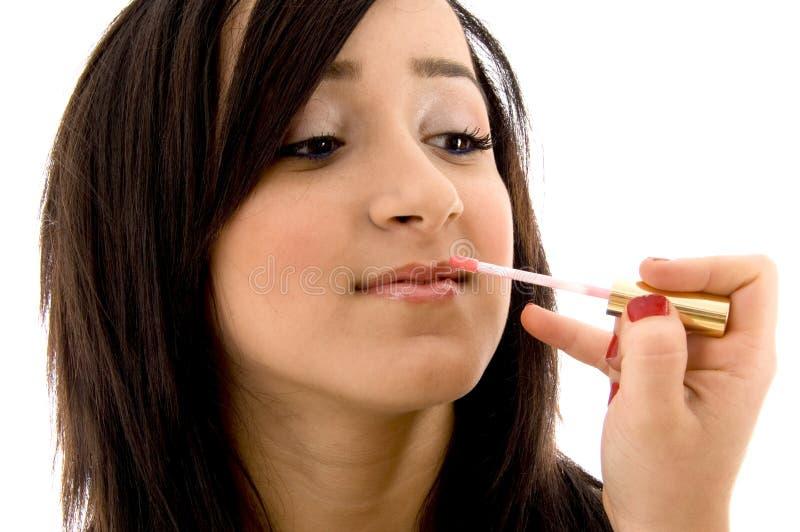 Beautician que pone el lápiz labial en hembra joven imagen de archivo