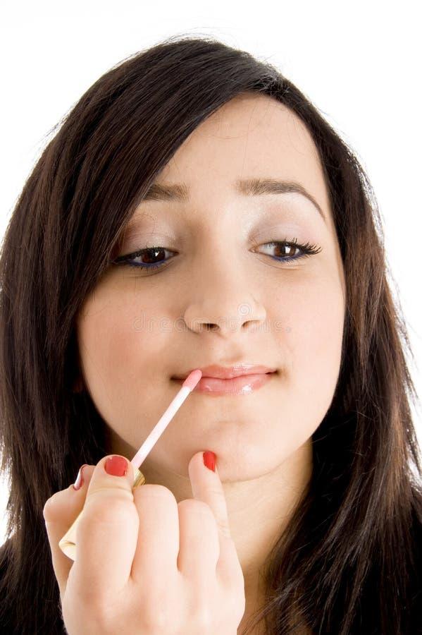 Beautician que pone el lápiz labial en modelo joven fotografía de archivo