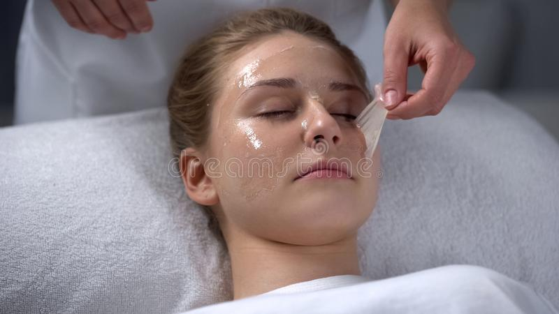 Beautician removing remains of mask from girls face, deep cleaning of pores. Stock photo stock photos