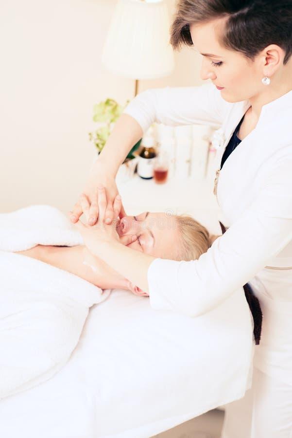 Beautician robi twarzowemu masażowi kosmetologia gabinet stosowanie opieki sk?ry przejrzystego lakier poj?cie zdrowego stylu ?yci fotografia stock