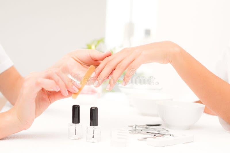 Beautician segregowania klientów żeńscy gwoździe przy zdroju piękna salonem obraz stock