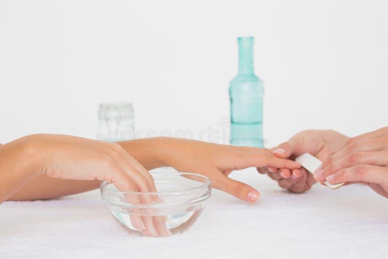 Beautician segregowania klienta żeńscy gwoździe przy zdroju piękna salonem zdjęcie stock