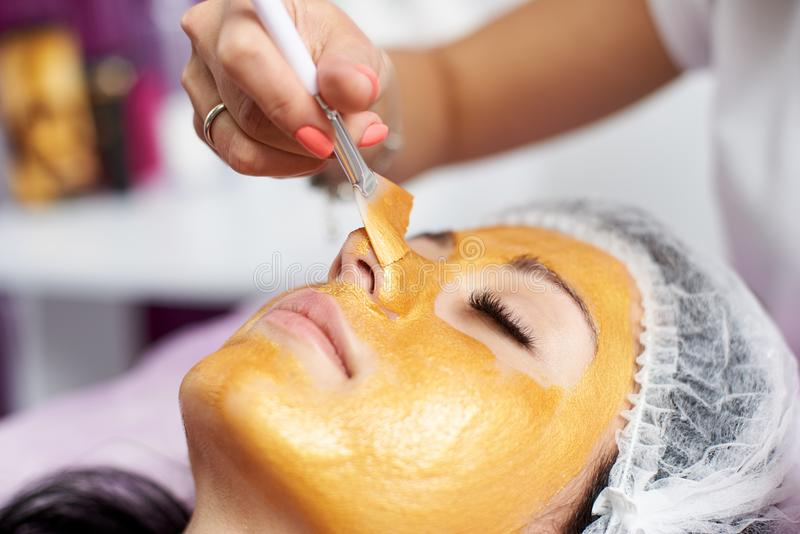 Beautician with special brush puts on face girl golden mask stock photos