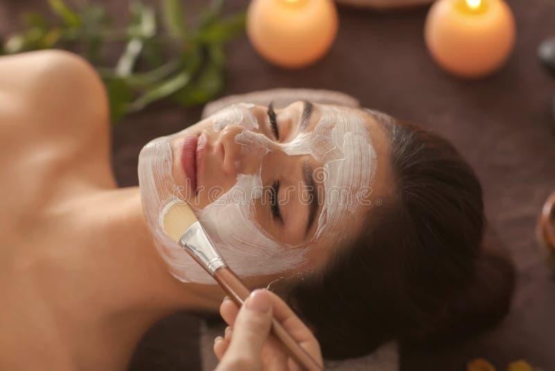 Beautician stosuje kosmetyk maskę na kobiety twarzy w zdroju salonie obrazy stock