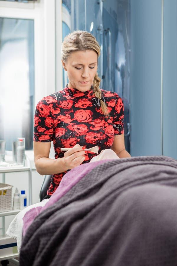 Beautician Stosuje twarzy śmietankę klient W salonie zdjęcia stock