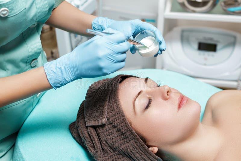 Beautician stosuje twarzy maskę na pięknej młodej kobiecie w zdroju salonie kosmetyczna procedury skóry opieka Microdermabrasion obraz royalty free