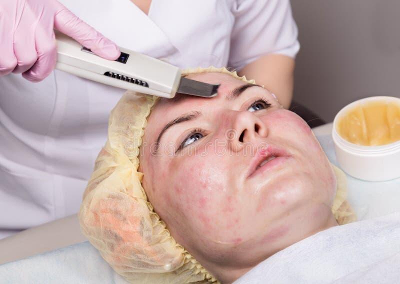Beautician sul lavoro Procedura di pulizia ultrasonica del fronte per la pelle di problema Immerga nella pulizia, saturazione del fotografia stock
