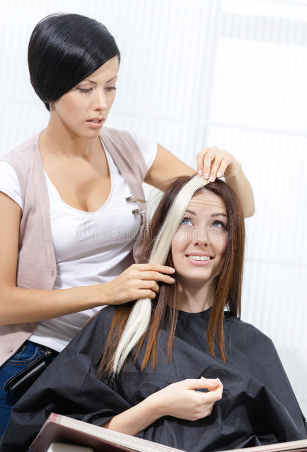 Beautician tries strand of dyed hair on the client royalty free stock photography