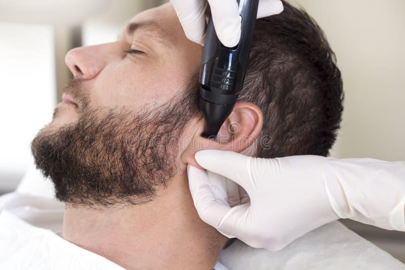 Beautician w salonie usuwa niepotrzebnego włosy od ucho mężczyzna fotografia royalty free
