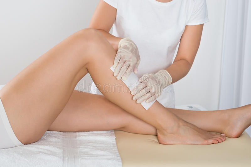 Beautician Waxing Leg Of Woman stock photography