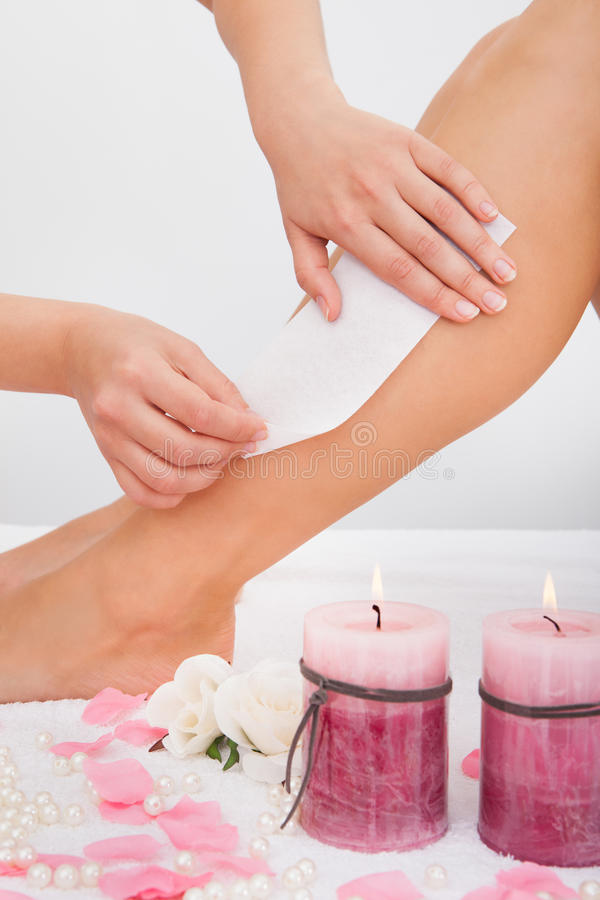 Beautician waxing a woman's leg royalty free stock photography