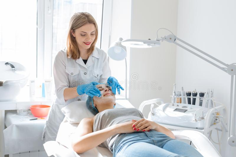 The beautician will break up the nourishing cream for the patient`s face mask. Moisturizing, cleaning and facial skin care. Cosmetic procedures royalty free stock photography