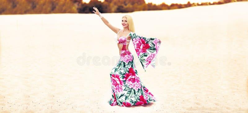 Beautidul het glimlachen dame het dansen Buikdans in de zandwoestijn royalty-vrije stock foto's