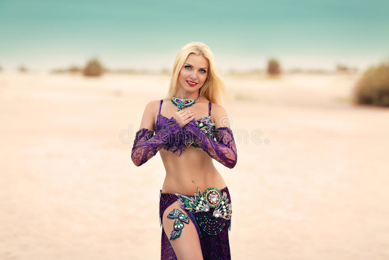 Beautidul het glimlachen dame het dansen Buikdans in de zandwoestijn stock foto's