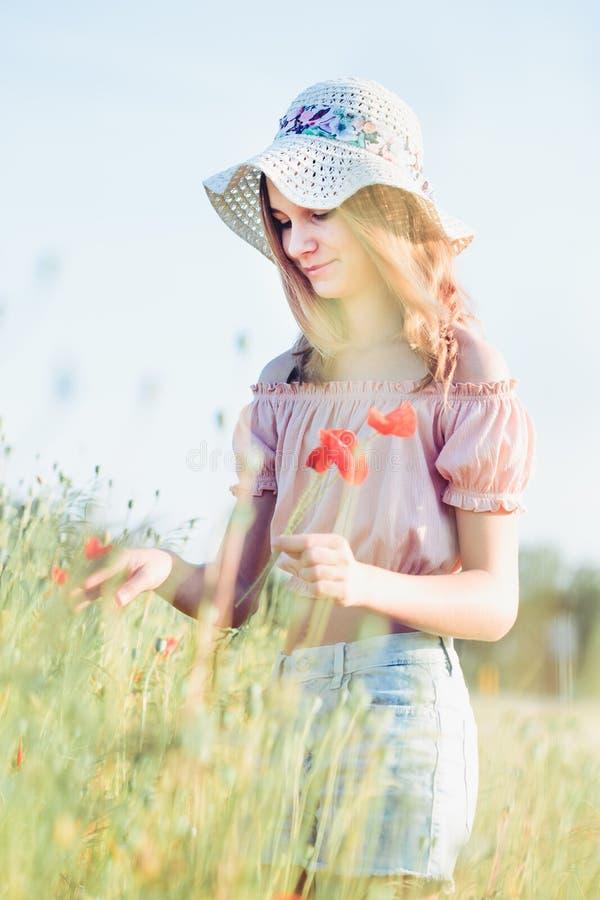 Beautieful ung flicka i fältet av lösa blommor arkivfoto